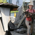 Woman carries her dog from Japan earthquake debris