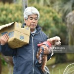 A man carries his dog from his home in Japan.